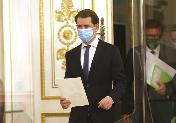 Austrian Chancellor Sebastian Kurz wearing a face mask to protect against coronavirus, walks at the federal chancellery in Vienna, Austria, Saturday, Nov. 14, 2020. The Austrian government has moved to restrict freedom of movement for people, in an effort to slow the onset of the COVID-19 coronavirus. (AP Photo/Ronald Zak)