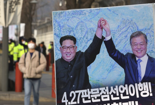 FILE - In this Jan. 15, 2019, file photo, a banner showing a photo of North Korean leader Kim Jong Un and South Korean President Moon Jae-in, right, is displayed to wish for peace on the Korean Peninsula, in Seoul, South Korea. South Korea's military fired warning shots Wednesday to repel a North Korean merchant ship after it violated their disputed western sea boundary, Seoul officials said, the second such incident in two months. (AP Photo/Ahn Young-joon/File)