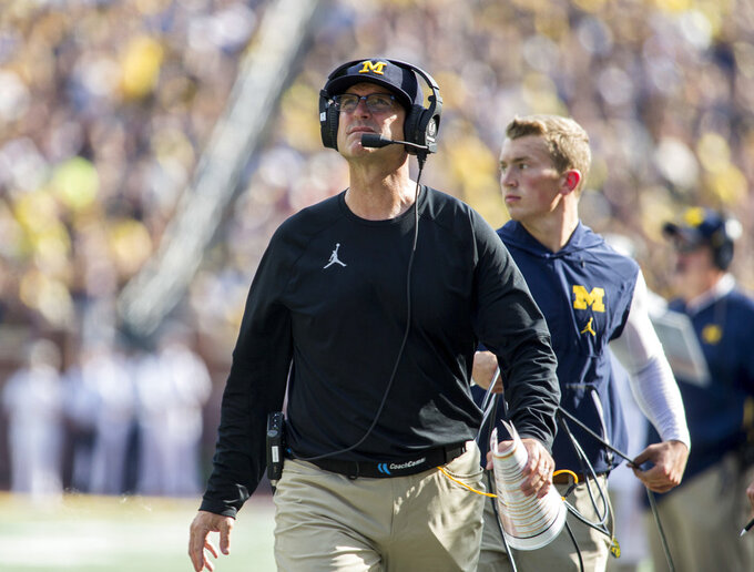 Michigan head coach Jim Harbaugh walks the sideline looking up at the scoreboard in the second quarter of an NCAA college football game against SMU in Ann Arbor, Mich., Saturday, Sept. 15, 2018. (AP Photo/Tony Ding)