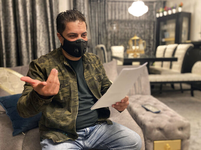 Samer Qraih, a Jordanian car dealer, sits in his apartment holding old business licences, bank statements and documents, in Amman, Jordan, Sunday, March 14, 2021. The 45-year-old, and father of four was sent to nine months in prison after he sank in into massive debts. Hundreds of thousands of Jordanians like Qraih are faced with incarceration because of draconian debt laws that violate international human rights law, according to the report published Tuesday by Human Rights Watch.  (AP Photo/Omar Akour)