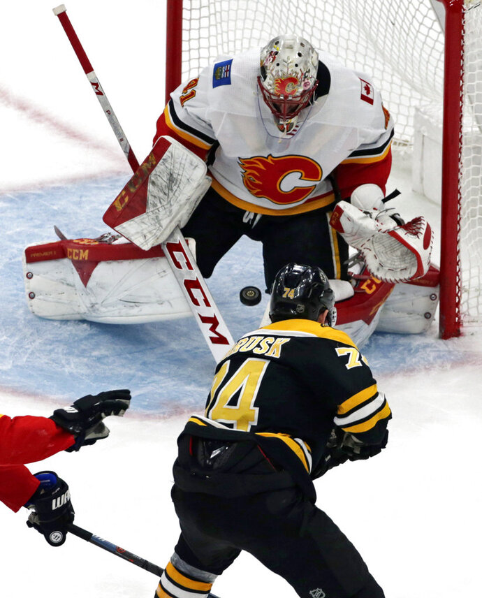 Boston Bruins left wing Jake DeBrusk (74) shoots the puck through the legs of Calgary Flames goaltender Mike Smith (41) for a goal in the third period of an NHL hockey game, Thursday, Jan. 3, 2019, in Boston. (AP Photo/Elise Amendola)