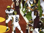 Michigan running back Hassan Haskins (25) celebrates a touchdown in the first half of an NCAA college football game Saturday, Oct. 24, 2020, in Minneapolis, Minn.  (Aaron Lavinsky/Star Tribune via AP)