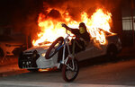 A protester on a bicycle rides past a burning police car during a demonstration next to the city of Miami Police Department, Saturday, May 30, 2020, downtown in Miami. Protests were held throughout the country over the death of George Floyd,  a black man who was killed in police custody in Minneapolis on May 25. (AP Photo/Wilfredo Lee)