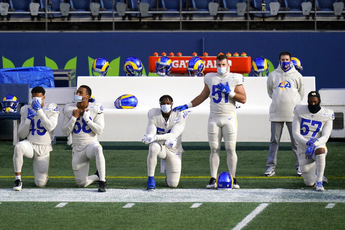 Los Angeles Rams players stand and kneel during the national anthem before an NFL football game against the Seattle Seahawks, Sunday, Dec. 27, 2020, in Seattle. (AP Photo/Elaine Thompson)