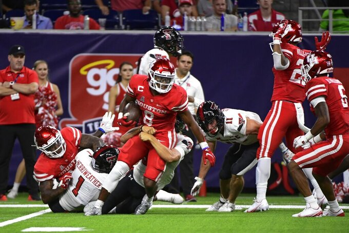 Houston running back Chandler Smith (8) is tackled by Texas Tech long snapper Jackson Knotts (30) during the second half of an NCAA college football game Saturday, Sept. 4, 2021, in Houston. (AP Photo/Justin Rex)