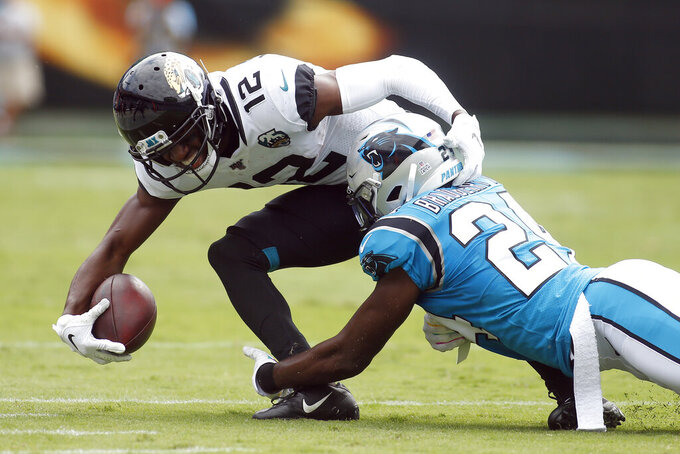 Carolina Panthers cornerback James Bradberry (24) tackles Jacksonville Jaguars wide receiver Dede Westbrook (12) during the first half of an NFL football game in Charlotte, N.C., Sunday, Oct. 6, 2019. (AP Photo/Brian Blanco)