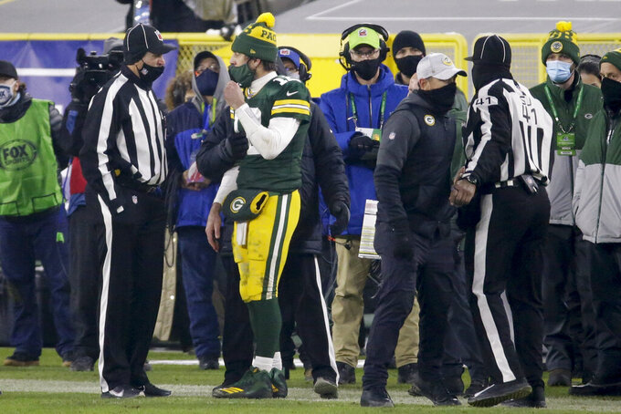 Green Bay Packers quarterback Aaron Rodgers talks to a game official during a referee time out during the second half of the NFC championship NFL football game against the Tampa Bay Buccaneers in Green Bay, Wis., Sunday, Jan. 24, 2021. (AP Photo/Mike Roemer)