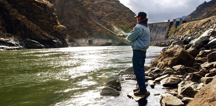 FILE - In this Nov. 16, 2003, file photo, fisherman Larry McBrom works along the Snake River shoreline below Hells Canyon Dam in southwestern Idaho. An Idaho utility will voluntarily dismiss its lawsuit against the U.S. Environmental Protection Agency involving relicensing of the company's hydroelectric project where federally protected fall chinook salmon reproduce. Idaho Power in documents filed recently in U.S. District Court says the EPA in response to the lawsuit has approved allowing warmer water temperatures in the Snake River below the Hells Canyon Complex on the Idaho-Oregon border. (Darin Oswald/The Idaho Statesman via AP, File)