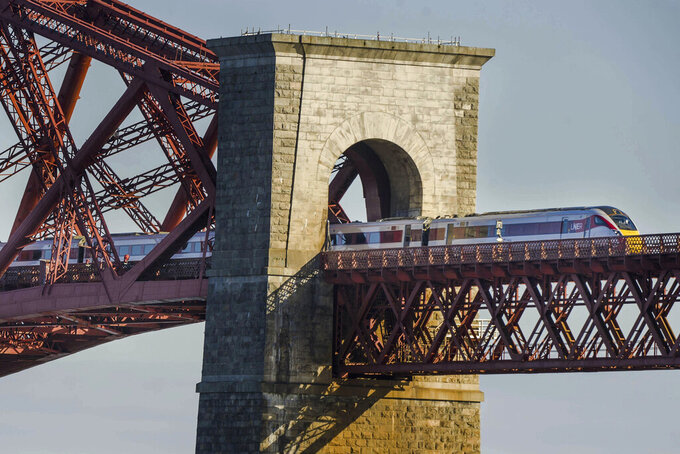FILE - In this May 6, 2021 file photo, a LNER Azuma train crossing the Forth Bridge in Edinburgh. Britain plans to bring the national rail network back under government control, reversing one of the most controversial elements of the privatization drive carried out by the Conservative governments of the 1980s and '90s. Under plans announced Thursday, May 20, 2021, the government will create a new entity known as Great British Railways that will own all railroad infrastructure, set most fares and schedules, collect ticket revenue and run a single ticketing website. Private companies will continue to operate trains under contracts with the state. (Euan Cherry/PA via AP, File)
