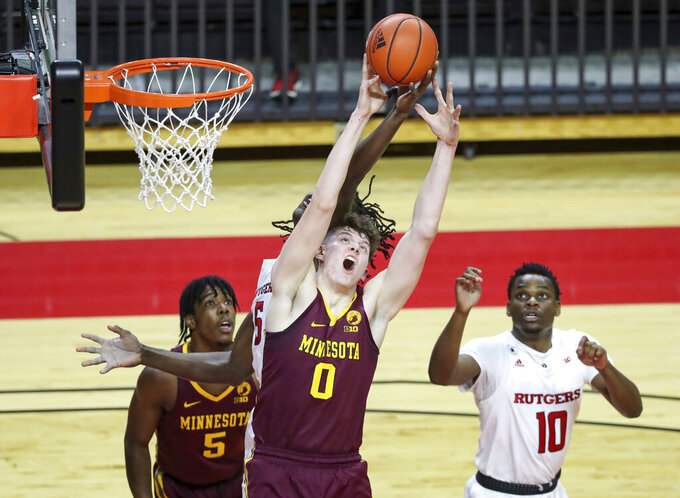 Minnesota center Liam Robbins (0) competes for a rebound with Rutgers center Cliff Omoruyi (5, obscured) during the first half of an NCAA college basketball game Thursday, Feb. 4, 2021, in Piscataway, N.J. (Andrew Mills/NJ Advance Media via AP)
