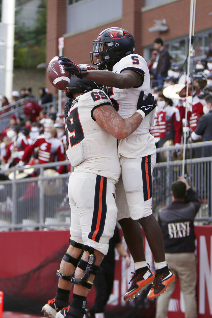 Oregon State running back Deshaun Fenwick (5) celebrates his touchdown with offensive lineman Nous Keobounnam (69) during the second half of an NCAA college football game against Washington State, Saturday, Oct. 9, 2021, in Pullman, Wash. Washington State won 31-24. (AP Photo/Young Kwak)