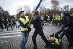 FILE - In this Nov. 24, 2018, file photo, Herve Ryssen, left, close to the ultra-right and convicted for antisemitic and racist comments, wearing a yellow jacket, clashes with riot police officers on the Champs-Elysees avenue in Paris. The offer by Italy's 5-Star Movement to share its web platform with France's