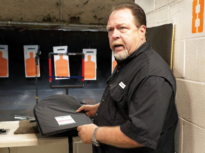 Steve Naremore, founder and CEO of TuffyPacks, handles one of his bulletproof panels that can be inserted into various makes and sizes of backpacks before a shooting demonstration of the stopping ability of the product at the Shiloh Shooting Range, Friday, August 9, 2019, in Houston. His company produces some bullet-resistant backpacks but the bulk of his business is in removable ballistic shields that are inserted in backpacks. (AP Photo/Michael Wyke)