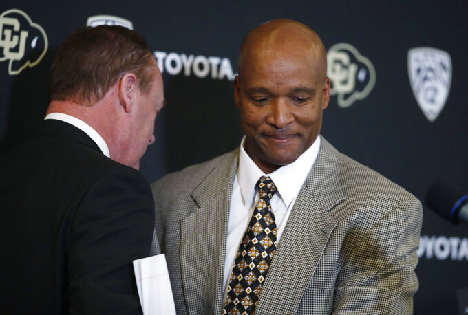 Karl Dorrell, right, is congratulated by athletic dirtector Rick George at a news conference to announce that Dorrell is the new NCAA college head football coach at Colorado during a news conference Monday, Feb. 24, 2020, in Boulder, Colo. (AP Photo/David Zalubowski)