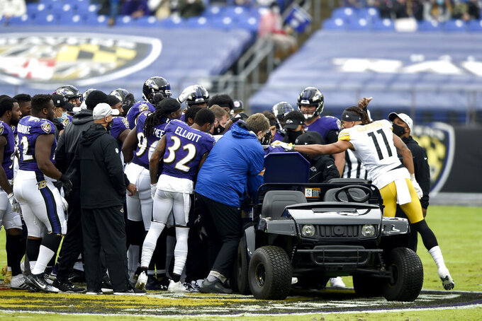 Pittsburgh Steelers wide receiver Chase Claypool (11) approaches a cart as Baltimore Ravens players surround offensive tackle Ronnie Stanley after he suffered an injury during the first half of an NFL football game, Sunday, Nov. 1, 2020, in Baltimore. (AP Photo/Gail Burton)