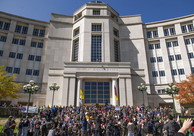 Open carry gun activist stand on the steps of the Michigan Hall of Justice on Thursday Sep. 17, 2020 in Lansing, Mich. (Nicole Hester/Ann Arbor News via AP)