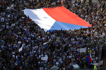 Protesters hold a large Czech flag as they gather at the Venceslas Square in Prague, Czech Republic, Tuesday, June 4, 2019. Thousands Czechs are rallying in Prague again to demand the resignation of justice minister, Marie Benesova, saying the new minister might compromise the legal system at a time when prosecutors have to decide whether to indict Prime Minister Andrej Babis over alleged fraud involving European Union funds. (AP Photo/Petr David Josek)