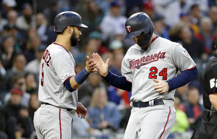 Minnesota Twins' Marwin Gonzalez greets C.J. Cron (24) after the two scored against the Seattle Mariners during the fifth inning of a baseball game Friday, May 17, 2019, in Seattle. (AP Photo/Elaine Thompson)