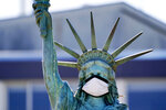 The face on a replica of the Statue of Liberty covers with a protective face mask against the coronavirus Wednesday, Aug. 26, 2020, in Seattle. The 1/18th scale replica on Seattle's Alki Beach was erected in 1952 and recast in 2006. (AP Photo/Elaine Thompson)