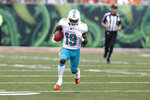 FILE - In this Oct. 7, 2018, file photo, Miami Dolphins wide receiver Jakeem Grant (19) returns a punt for a touchdown against the Cincinnati Bengals during the first half of an NFL football game in Cincinnati. Grant has signed a four-year contract extension worth up to $24 million through the 2023 season. The Dolphins announced the extension on Wednesday, Aug. 21, 2019. (AP Photo/Frank Victores, File)