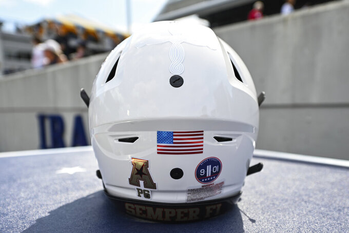 A Navy football helmet with 9/11 decals sits on the sideline before an NCAA college football game against Air Force, Saturday, Sept. 11, 2021, in Annapolis, Md. (AP Photo/Terrance Williams)