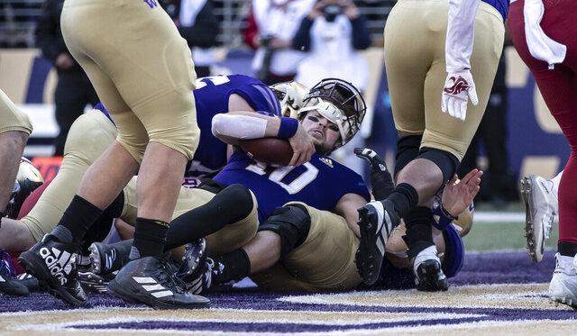 Washington quarterback Jacob Eason scores a touchdown during the first half an NCAA college football game against Washington State, on Friday, Nov. 29, 2019 in Seattle. (AP Photo/Stephen Brashear)