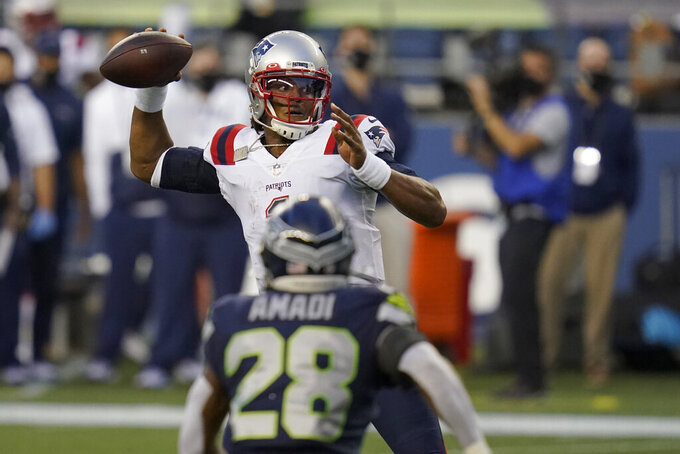 New England Patriots quarterback Cam Newton passes as Seattle Seahawks safety Ugo Amadi looks on during the second half of an NFL football game, Sunday, Sept. 20, 2020, in Seattle. (AP Photo/Elaine Thompson)