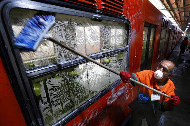 A member of cleaning crew washes metro car as a preventive measure against the spread of the new coronavirus in Mexico City, Wednesday, March 18, 2020. For most people COVID-19 causes mild or moderate symptoms. For others, especially the elderly and people with existing health problems, it can cause many other serious illnesses, including pneumonia. (AP Photo/Marco Ugarte)