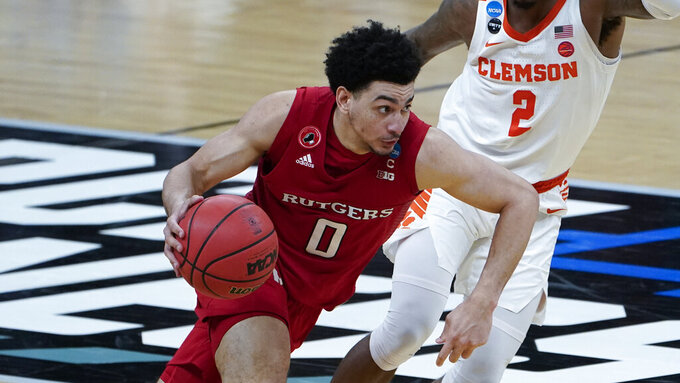 FILE - In this March 19, 2021, file photo, Rutgers guard Geo Baker (0) plays against Clemson during the second half of a men's college basketball game in the first round of the NCAA tournament in Indianapolis. Rutgers of the Big Ten Conference made the NCAA Tournament last season for the first time since 1991. The Scarlet Knights defeated Clemson in the opening round of the tournament and lost to Houston in the second round. (AP Photo/Paul Sancya, File)