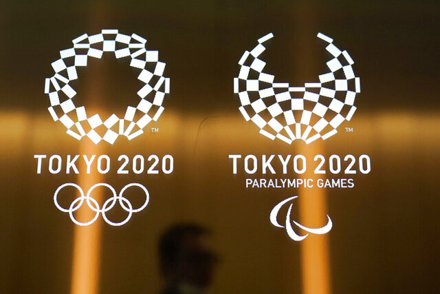 FILE - In this June 11, 2019, file photo, a man walks past the logos of the Tokyo 2020 Paralympics and Olympics in Tokyo. On Thursday, Dec. 12, 2019, the International Paralympic Committee confirmed the Paralympic marathons are staying in Tokyo, unlike the marathons for the Olympics, which have been moved north to the cooler city of Sapporo. (AP Photo/Jae C. Hong, File)