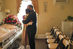 Siblings Erika and Dwayne Bermudez comfort one another during a short viewing of their mother, Eudiana Smith, at The Family Funeral Home, Saturday, May 2, 2020, in Newark, N.J. (AP Photo/Seth Wenig)