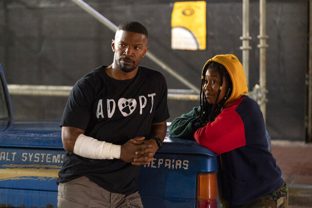 This image released by Netflix shows Jamie Foxx, left, and Dominique Fishback in a scene from