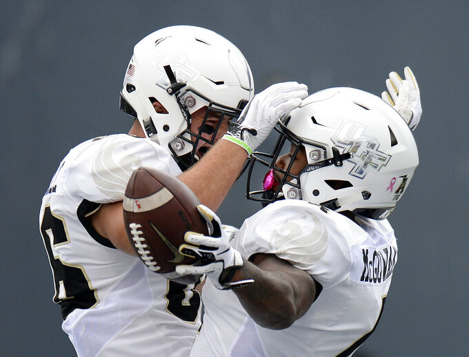 Central Florida running back Taj McGowan, right, celebrates with tight end Michael Colubiale (86) after McGowan scored a touchdown on a 2-yard run against Memphis during the first half of an NCAA college football game Saturday, Oct. 13, 2018, in Memphis, Tenn. (AP Photo/Mark Zaleski)