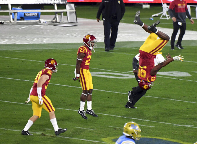 Southern California players, including Drake Jackson (99), celebrate a win over UCLA in an NCAA college football game Saturday, Dec. 12, 2020, in Pasadena, Calif. (Keith Birmingham/The Orange County Register via AP)
