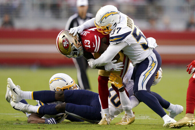 San Francisco 49ers wide receiver Richie James Jr. (13) is tackled by Los Angeles Chargers outside linebacker Jatavis Brown (57) and defensive back Brandon Facyson during the first half of an NFL preseason football game in Santa Clara, Calif., Thursday, Aug. 29, 2019. (AP Photo/Tony Avelar)