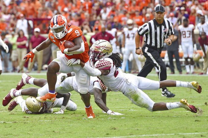Clemson's Travis Etienne (9) runs out of the tackle attempt by Florida State's Akeem Dent during the first half of an NCAA college football game Saturday, Oct. 12, 2019, in Clemson, S.C. (AP Photo/Richard Shiro)