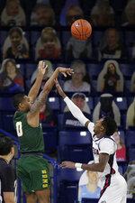 San Francisco guard Khalil Shabazz, left, shoots over Gonzaga guard Joel Ayayi during the first half of an NCAA college basketball game in Spokane, Wash., Saturday, Jan. 2, 2021. (AP Photo/Young Kwak)