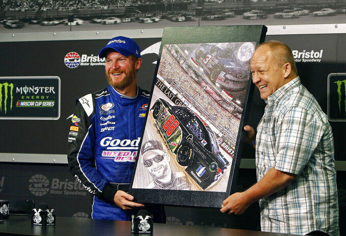 FILE - In this Aug. 17, 2017, file photo, NASCAR driver Dale Earnhardt Jr., left, stands with artist Sam Bass as he's presented with an original painting during a press conference at Bristol Motor Speedway in Bristol, Tenn. Bass, NASCAR's first officially licensed artist, has died following a battle with kidney problems. He was 57.   (AP Photo/Wade Payne, File)