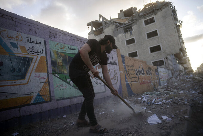 People clean the streets of debris beside a building that was previously damaged in an air-strike following a cease-fire reached after an 11-day war between Gaza's Hamas rulers and Israel, in Gaza City, Friday, May 21, 2021. (AP Photo/John Minchillo)