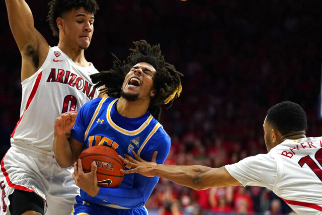 UCLA guard Tyger Campbell (10) drives between Arizona's Josh Green (0) and Jemarl Baker Jr. during the first half of an NCAA college basketball game Saturday, Feb. 8, 2020, in Tucson, Ariz. (AP Photo/Rick Scuteri)