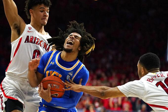 UCLA guard Tyger Campbell (10) drives between Arizona's Josh Green (0) and Jemarl Baker Jr. during the first half of an NCAA college basketball game Saturday, Feb. 8, 2020, in Tucson, Ariz. (AP Photo/Rick Scuteri)