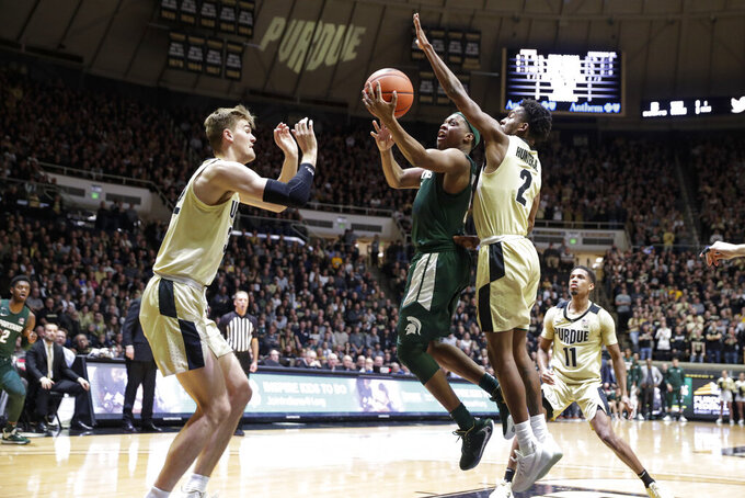 Michigan State guard Cassius Winston (5) shoots between Purdue guard Eric Hunter Jr. (2) and center Matt Haarms (32) during the first half of an NCAA college basketball game in West Lafayette, Ind., Sunday, Jan. 12, 2020. (AP Photo/Michael Conroy)