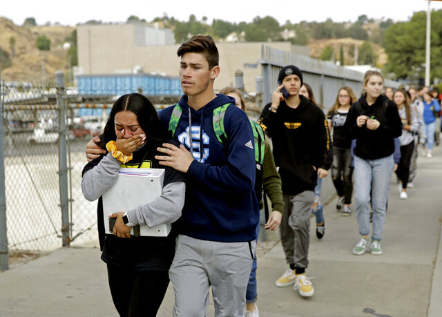 FILE - This Nov. 14, 2019 file photo shows students being escorted out of Saugus High School after a shooting on the campus in Santa Clarita, Calif. Authorities say the teenager who shot five classmates, killing two, at a Southern California high school used an unregistered
