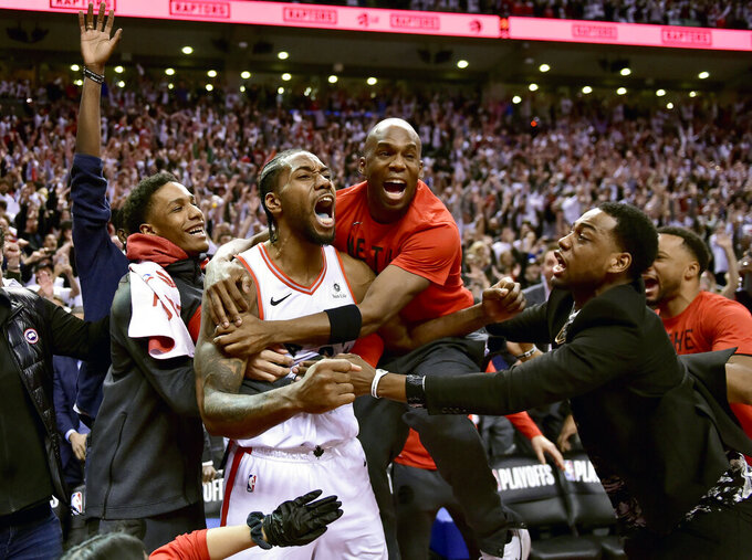 FILE - In this May 12, 2019, file photo, Toronto Raptors forward Kawhi Leonard, second from left, celebrates his game-winning basket as time expired at the end of an NBA Eastern Conference semifinal basketball game against the Philadelphia 76ers, in Toronto on Sunday,. Toronto won 92-90. (Frank Gunn/The Canadian Press via AP, File)