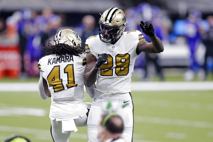 New Orleans Saints running back Alvin Kamara (41) celebrates his second touchdown with running back Latavius Murray (28) in the first half of an NFL football game against the Minnesota Vikings in New Orleans, Friday, Dec. 25, 2020. (AP Photo/Brett Duke)