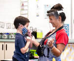 A student gets help with his mask from transitional kindergarten teacher Annette Cuccarese during the first day of classes at Tustin Ranch Elementary School in Tustin, Calif., on Thursday, Aug. 12, 2021. (Paul Bersebach/The Orange County Register via AP)