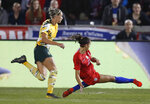 United States forward Alex Morgan, right, falls while scoring a goal as Australia defender Alanna Kennedy looks on during the first half of a friendly soccer match Thursday, April 4, 2019, in Commerce City, Colo. (AP Photo/David Zalubowski)