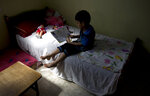 In this May 27, 2019, photo, Abdelrahman, brother of 5-year-old Aisha a-Lulu, sits on what used to be Aisha's bed, at the family home in Burij refugee camp in central Gaza Strip. The death of the 5-year-old Palestinian girl has drawn attention to Israel's vastly complex system for issuing travel permits to Gaza medical patients and their families. (AP Photo/Hatem Moussa)