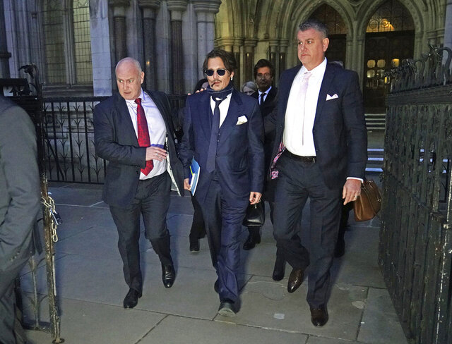 Actor Johnny Depp, center, leaves the High Court in London, after attending a preliminary hearing in his libel case against the publishers of The Sun and its executive editor, Dan Wootton, over a 2018 article alleging he had been abusive to his ex-wife Amber Heard, Wednesday, Feb. 26, 2020. (Aaron Chown/PA via AP)