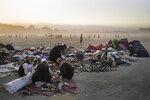 Afghans sort second-hand clothes at the Chaman-e-Hozari Park in Kabul, Afghanistan, Friday, Sept. 17, 2021. (AP Photo/Bernat Armangue)